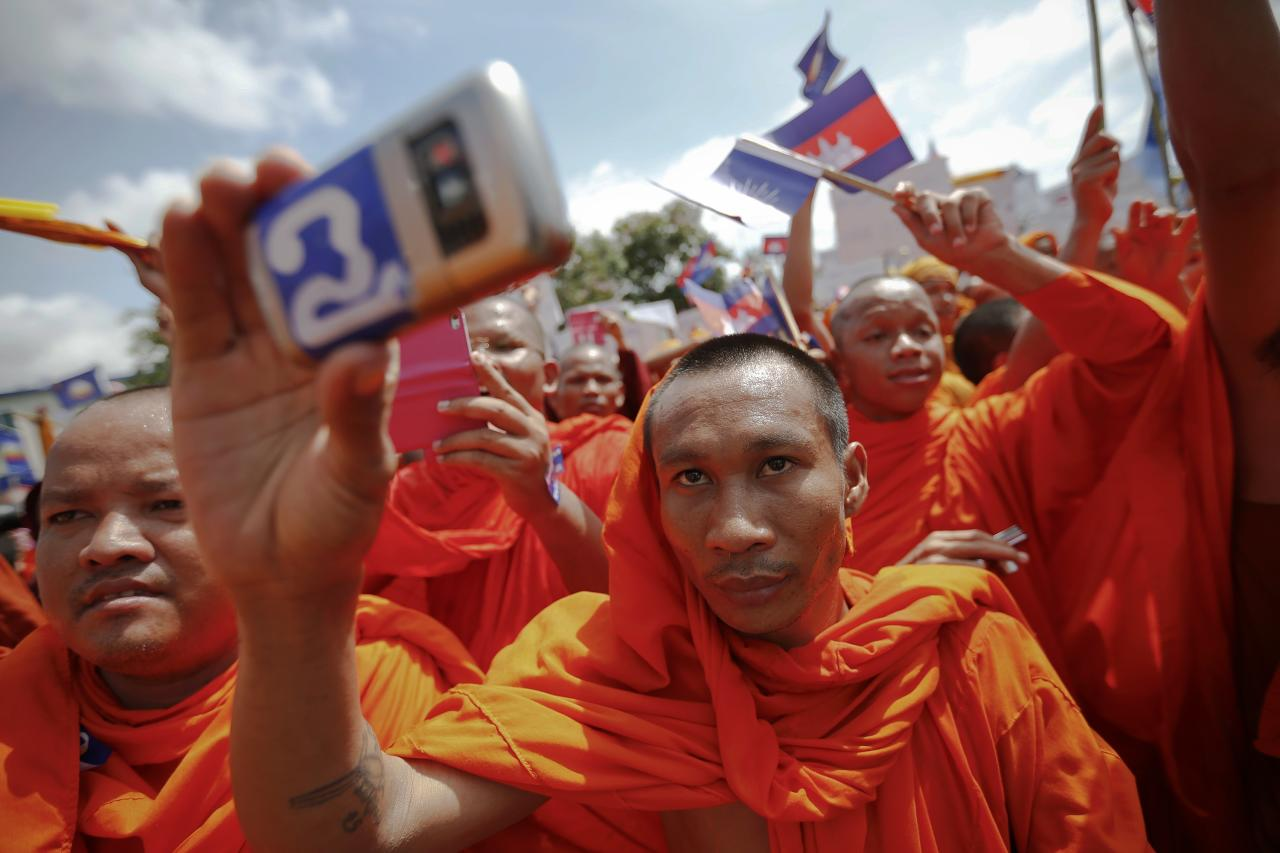 A Buddhist monk records the speech of one of the leaders of Cambodia National Rescue Party (CNRP) during a rally in Phnom Penh