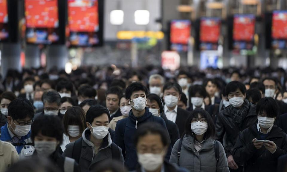 Commuters make their way to work in Tokyo on 26 March