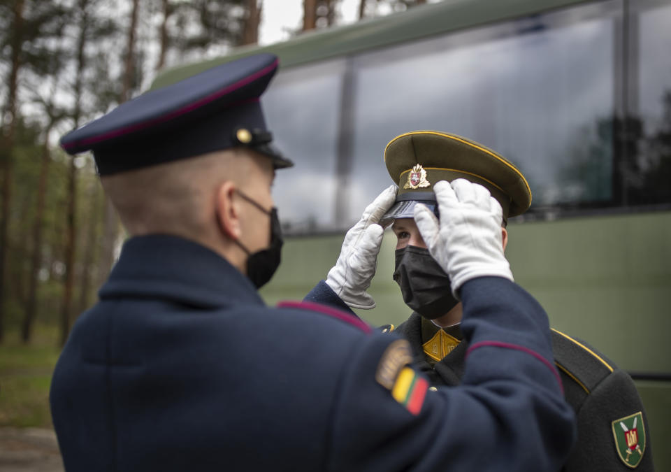 Lithuanian soldiers of the honour guard, wearing face masks to prevent the spread of coronavirus, prepare to attend a ceremony marking the 76th anniversary of the end of World War II at the Paneriai memorial, Vilnius, Lithuania, Saturday, May 8, 2021. Victory in Europe Day is celebrated on May 8 to mark the date in 1945 that WWII ended in Europe following Nazi Germany's surrender of its armed forces. (AP Photo/Mindaugas Kulbis)