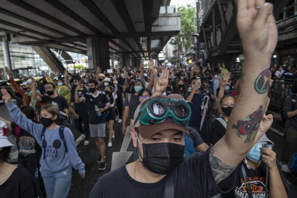 Pro-democracy protesters flash three-fingered salute during a protest in Udom Suk, suburbs of Bangkok, Thailand, Saturday, Oct. 17, 2020. The authorities in Bangkok shut down mass transit systems and set up roadblocks Saturday as Thailand's capital faced a fourth straight day of determined anti-government protests. (AP Photo/Gemunu Amarasinghe)
