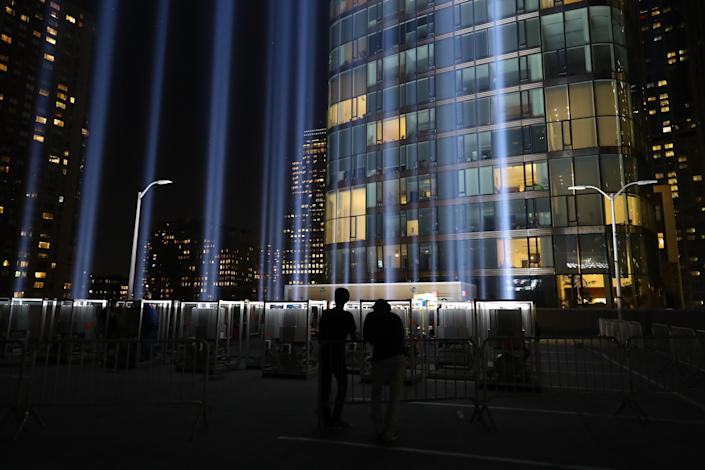 <p>Volunteers watch the beam of light from the Tribute in Light rise above the New York City skyline on Sept. 5, 2018. (Photo: Gordon Donovan/Yahoo News) </p>