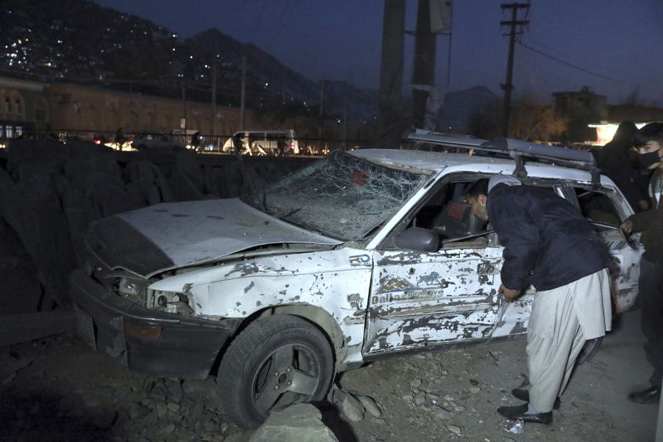 An Afghan man inspects the site of a bomb attack in Kabul, Afghanistan, Monday, Dec. 28, 2020. (AP Photo/Rahmat Gul)