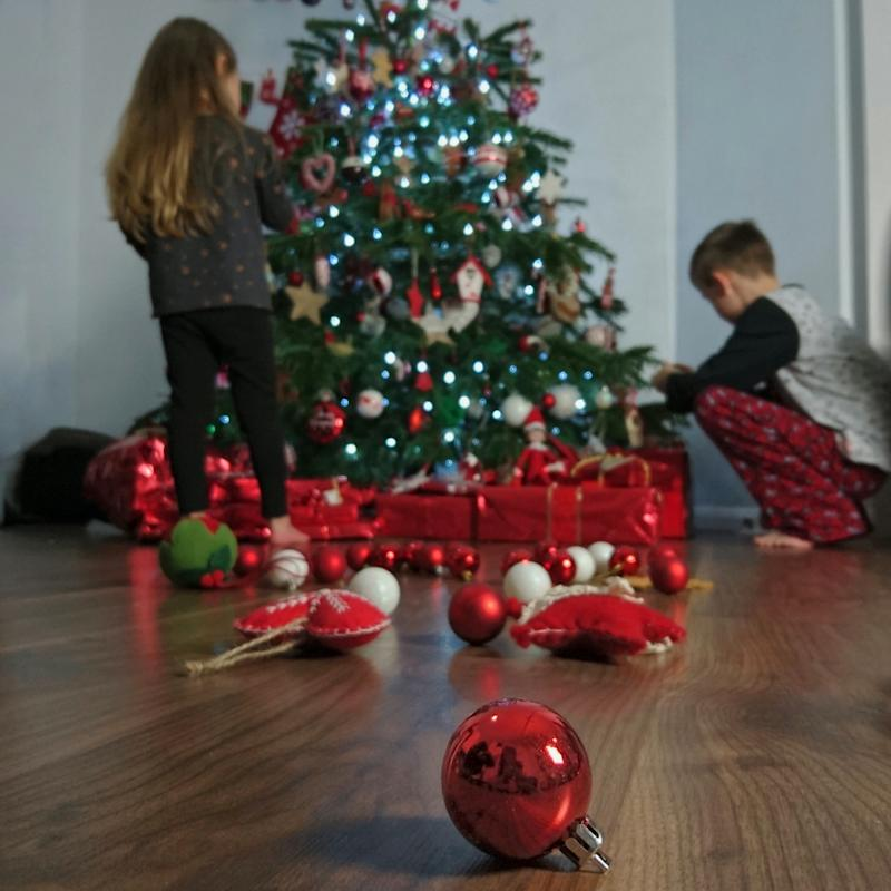 Kids at a Christmas tree as social worker tells parents not to give expensive presents from Santa.