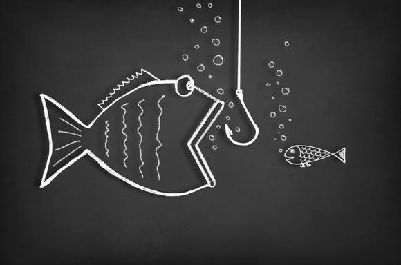 A small fish looks on as a bigger fish with an open mouth moves toward a hook on a line.
