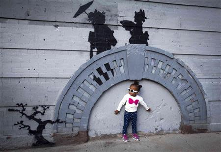 A child poses for a photo under a new art piece by British graffiti artist Banksy in the Brooklyn borough of New York, October 17, 2013. REUTERS/Carlo Allegri