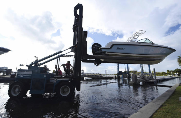 <p>Daniel Elkins, left, of Marine Max, lifts a boat out of the water in preparation of Hurricane Florence in Wrightsville Beach, N.C., Tuesday, Sept. 11, 2018. (Photo: Matt Born/The Star-News via AP) </p>