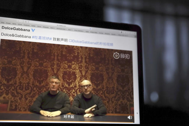 """FILE - In this Nov. 23, 2018, file photo, founders of Dolce&Gabbana Domenico Dolce, left and Stefano Gabbana apologize in a video on Chinese social media, saying """"sorry"""" in Mandarin seen on a computer screen in Beijing, China. Don't mess with China - and its 770 million internet users. That's the lesson Dolce&Gabbana learned the hard way after Chinese netizens expressed their outrage at a promotional video the company made for the Chinese market and insulting comments made on Instagram, though the company blamed hackers for the latter. As retailers pulled their merchandise from shelves, co-founders Domenico Dolce and Stefano Gabbana went on camera to apologize to the Chinese people. (AP Photo/Ng Han Guan, File)"""