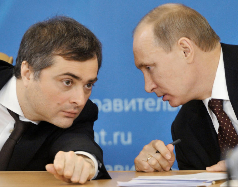 FILE In this file photo taken on Tuesday, March 18, 2014, Russian Prime Minister Vladimir Putin, right, speaks to Vladislav Surkov, deputy prime minister in charge of economic modernization, during a visit in Kurgan, Russia. A former senior aide to Russian President Vladimir Putin has warned that Ukraine will never be able to regain control over the separatist-controlled east. Vladislav Surkov, who lost his job as Putin's adviser on Ukraine earlier this month, said in remarks published Wednesday, Feb. 26, 2020 that he stepped down because of a shift in the Kremlin course on the Ukrainian conflict. (Alexei Nikolsky, Sputnik, Kremlin Pool Photo via AP, File)