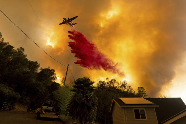 FILE - In this Aug. 18, 2020, file photo, an air tanker drops retardant as the LNU Lightning Complex fires tear through the Spanish Flat community in unincorporated Napa County, Calif. Two unusual weather phenomena combined to create some of the most destructive wildfires the West Coast states have seen in modern times. (AP Photo/Noah Berger, File)