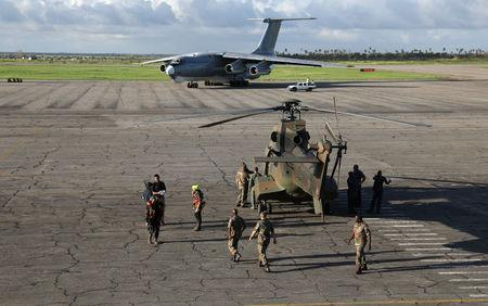 Members of the South African Defence Force (SANDF) are seen with rescue workers near a helicopter at an airport in Beira, Mozambique, March 22, 2019. REUTERS/Siphiwe Sibeko