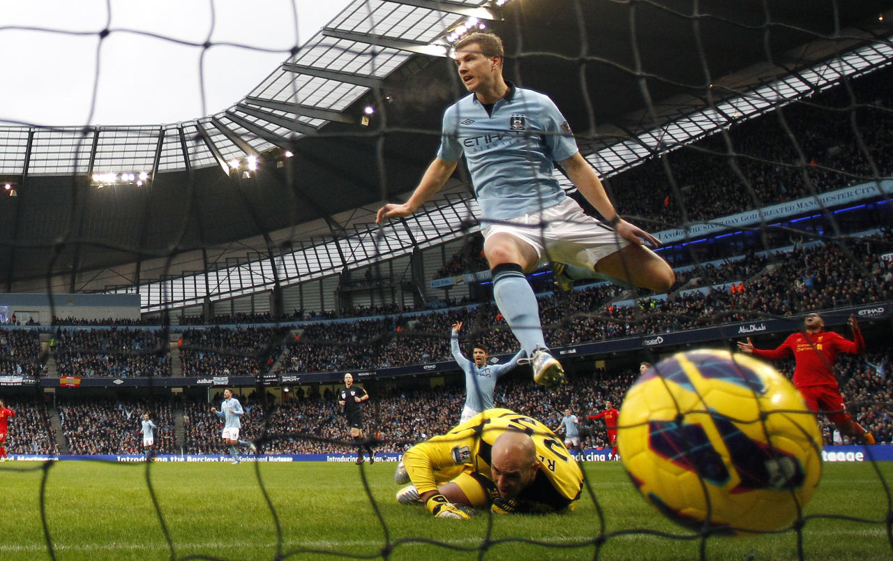 "Manchester City's Edin Dzeko (top) celebrates after scoring during their English Premier League soccer match against Liverpool at the Etihad Stadium in Manchester, northern England February 3, 2013. REUTERS/Phil Noble (BRITAIN - Tags: SPORT SOCCER TPX IMAGES OF THE DAY) FOR EDITORIAL USE ONLY. NOT FOR SALE FOR MARKETING OR ADVERTISING CAMPAIGNS. NO USE WITH UNAUTHORIZED AUDIO, VIDEO, DATA, FIXTURE LISTS, CLUB/LEAGUE LOGOS OR ""LIVE"" SERVICES. ONLINE IN-MATCH USE LIMITED TO 45 IMAGES, NO VIDEO EMULATION. NO USE IN BETTING, GAMES OR SINGLE CLUB/LEAGUE/PLAYER PUBLICATIONS - RTR3DAZR"