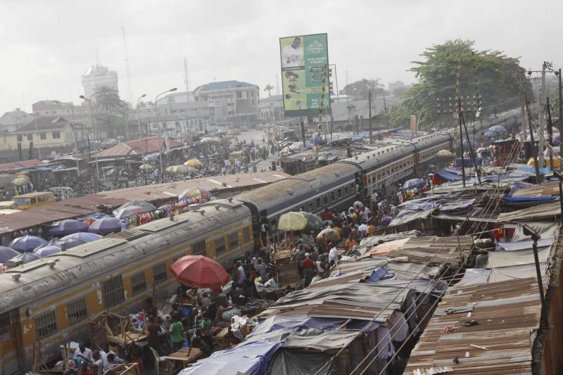 In this Wednesday, March 2, 2011 photo, a passenger train passes through the Yaba neighborhood of Lagos, Nigeria. Railroad officials hope a $166 million plan will bring the rebirth of the long-moribund Nigerian Railway Corp., just in time for an election in April. But it's far from clear whether the railway will be a success or just another broken promise. (AP Photo/Sunday Alamba)