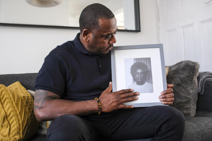 Lee Lawrence poses with a picture of his mother, Cherry Groce, in London, Wednesday, April 21, 2021. Lawrence's mother, Cherry Groce, was shot by police during a raid on her London home in 1985. She was left paralyzed from the waist down and died in 2011 after spending 26 years in a wheelchair. Her shooting triggered the 1985 Brixton riots, and her family have been fighting for justice ever since. (AP Photo/Alberto Pezzali)