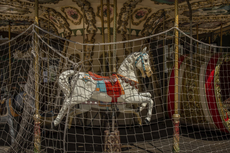 A closed carousel due to the COVID-19 pandemic in Madrid, Spain, Wednesday, May 27, 2020. Spain has become the first western Europe to accumulate more than 1 million confirmed infections as the country of 47 million inhabitants struggles to contain a resurgence of the coronavirus. (AP Photo/Bernat Armangue)