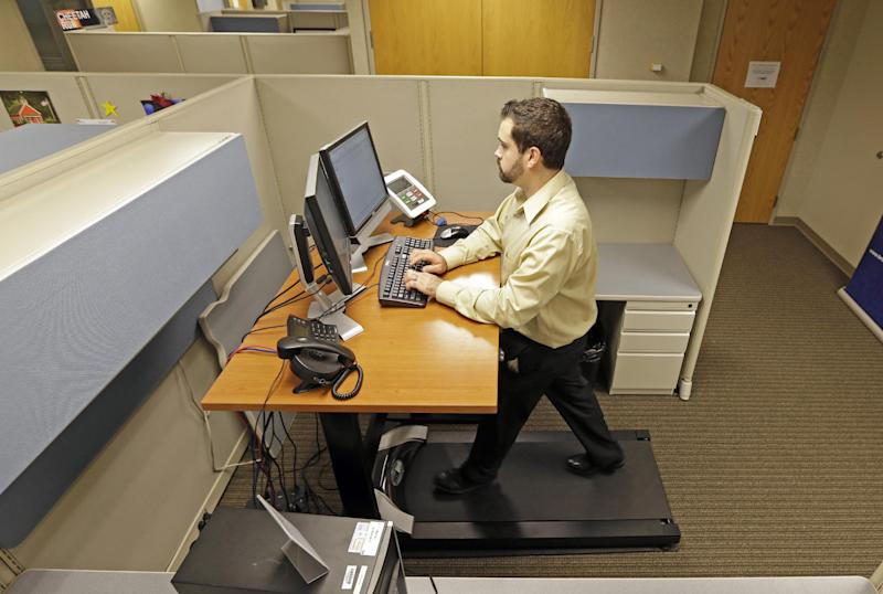 Josh Baldonado, an administrative assistant at Brown & Brown Insurance, works at a treadmill desk in the firms offices in Carmel, Ind., Wednesday, Aug. 28, 2013. Workers sign up for 30 slots not he treadmills and have their phone and computer transferred to the workstations. Being glued to your desk is no longer an excuse for not having time to exercise as a growing number of Americans are standing, walking and even cycling their way through the work day at treadmill desks, standup desks or other moving work stations. (AP Photo/Michael Conroy)