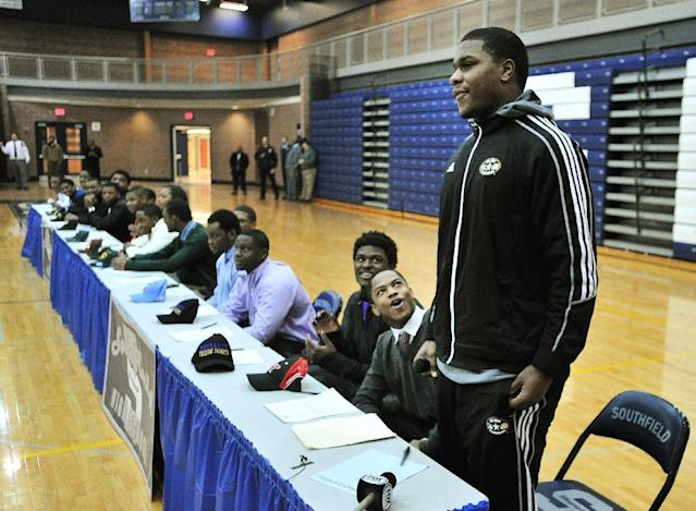 Teammates and schoolmates react after Malik McDowell, right, announces he will be attending Michigan State University to play football during a national signing day ceremony at Southfield High School's gym in Southfield, Mich., Wednesday, Feb. 5, 2014. (AP Photo/Detroit News, Daniel Mears )