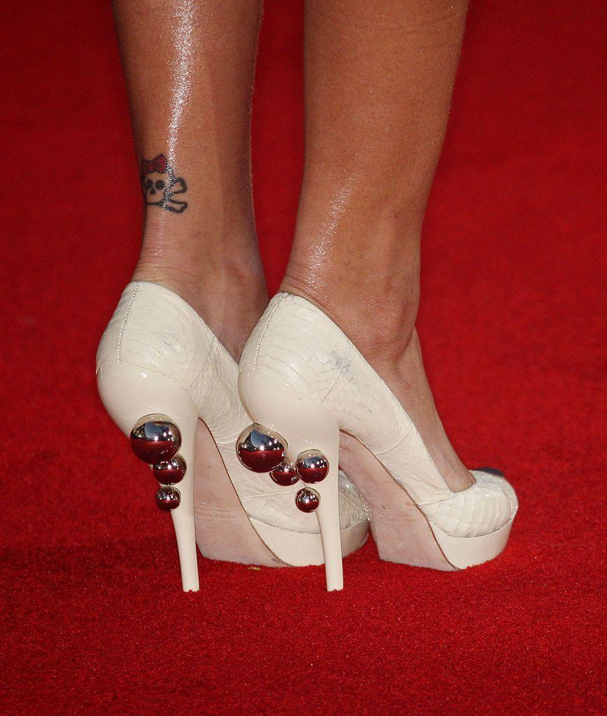 <p>On the back of her right leg, Rihanna has a skull and crossbones which was given a feminine twist with a red bow.</p>