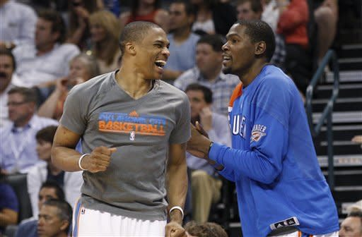 Oklahoma City Thunder guard Russell Westbrook, left, and forward Kevin Durant react after a Thunder basket during the third quarter of an NBA basketball game against the Sacramento Kings in Oklahoma City, Tuesday, April 24, 2012. Oklahoma City won 118-110. (AP Photo/Sue Ogrocki)