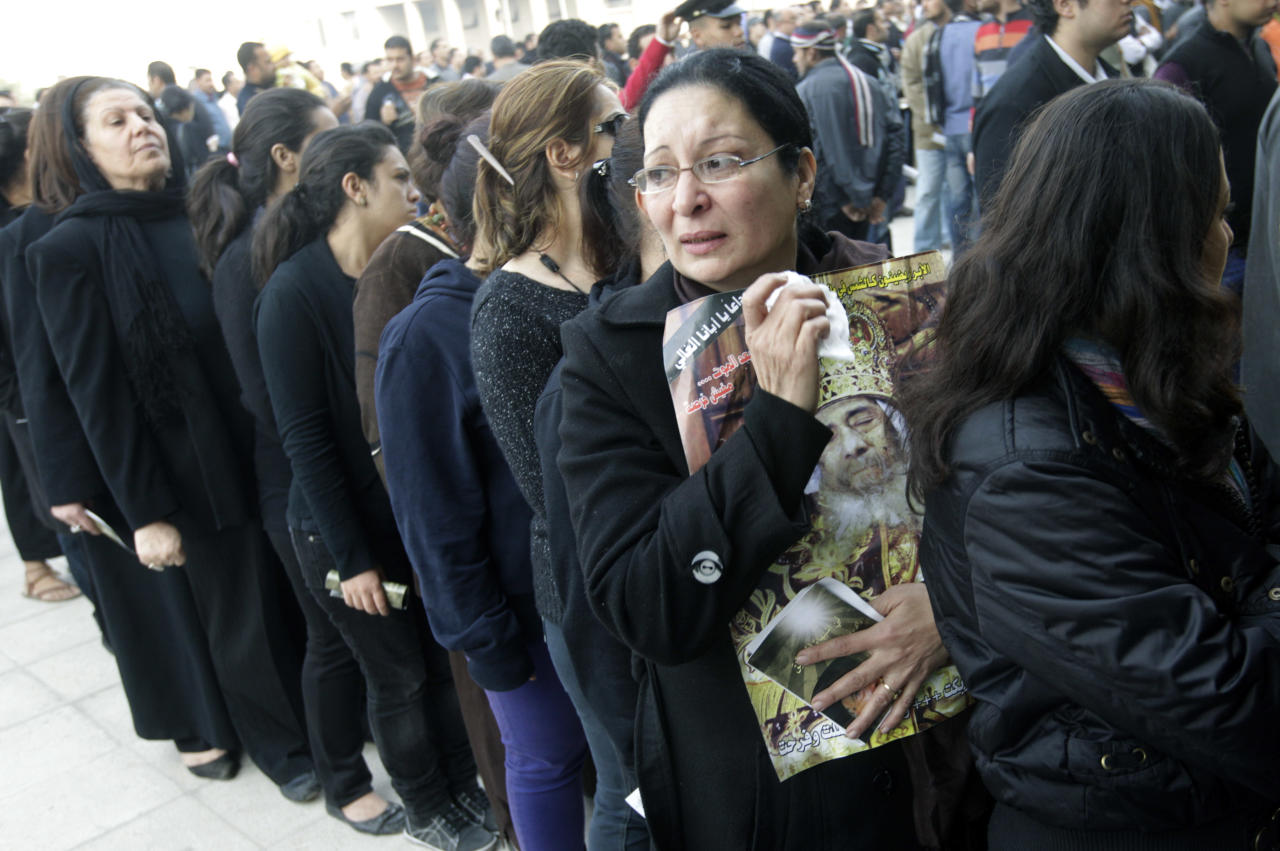 An Egyptian Christian woman carries a poster of the late Pope Shenouda III, the patriarch of the Coptic Orthodox Church who led Egypt's Christian minority for 40 years during a time of increasing tensions with Muslims, as others line up to enter his funeral at Mar Morqos, or St. Mark Coptic Orthodox Church in Cairo, Egypt, Tuesday, March 20, 2012. (AP Photo/Amr Nabil)