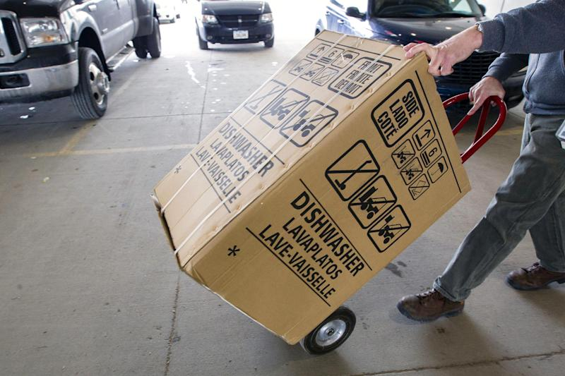 In this Wednesday, Feb. 27, 2013, photo, an employees carts a dishwasher to a customer's vehicle at the loading docks of Nebraska Furniture Mart in Omaha, Neb. U.S. orders for long-lasting goods that signal business investment plans fell in February by the largest amount in seven months, although the decline followed a strong month in January and may prove to be a temporary setback. (AP Photo/Nati Harnik)