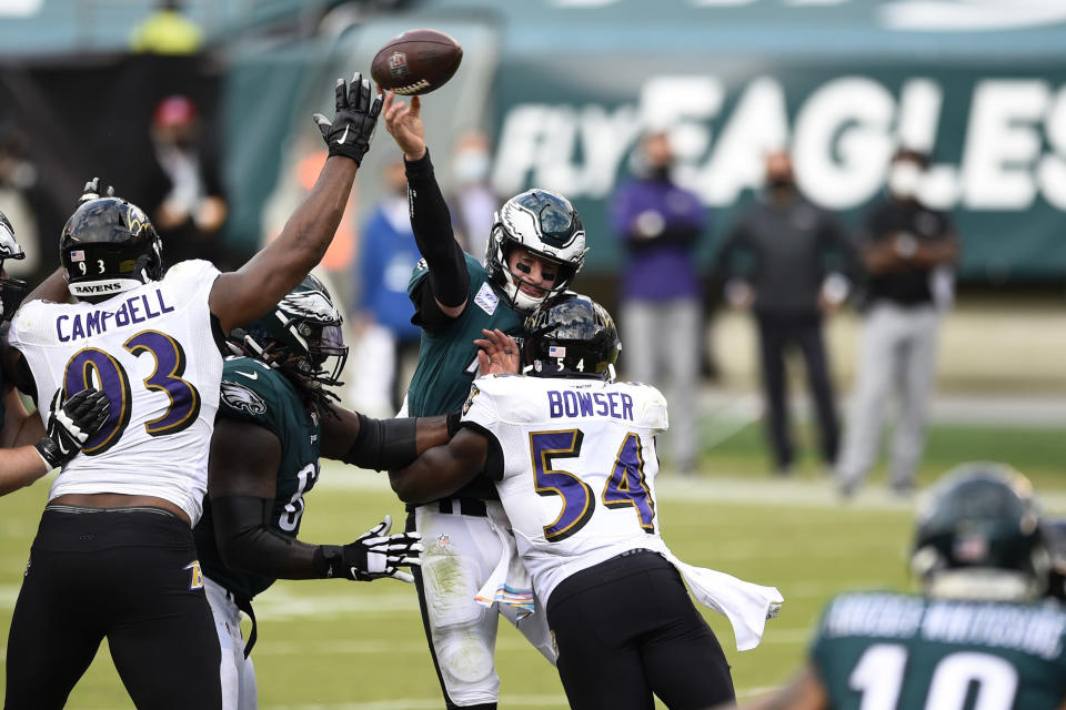 Philadelphia Eagles' Carson Wentz (11) tries to pass against Baltimore Ravens' Tyus Bowser (54) and Calais Campbell (93) during the second half of an NFL football game, Sunday, Oct. 18, 2020, in Philadelphia. (AP Photo/Derik Hamilton)