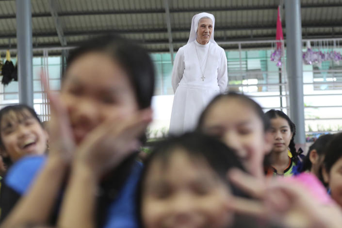 In this Aug. 27, 2019, photo, ST. Mary's School Vice Principal Sister Ana Rosa Sivori, rear, watches students play during a lunch break at the girls' school in Udon Thani, about 570 kilometers (355 miles) northeast of Bangkok, Thailand. Sister Ana Rosa Sivori, originally from Buenos Aires in Argentina, shares a great-grandfather with Jorge Mario Bergoglio, who, six years ago, became Pope Francis. So, she and the pontiff are second cousins. (AP Photo/Sakchai Lalit)