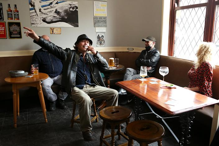 BOLTON, ENGLAND - MAY 17: A man is seen playing a harmonica while enjoying a pint in The Greyhound Pub as indoor hospitality reopens on May 17, 2021 in Bolton, England. UK Health Secretary Matt Hancock said during a TV interview yesterday that a the government will consider a local lockdown in Bolton