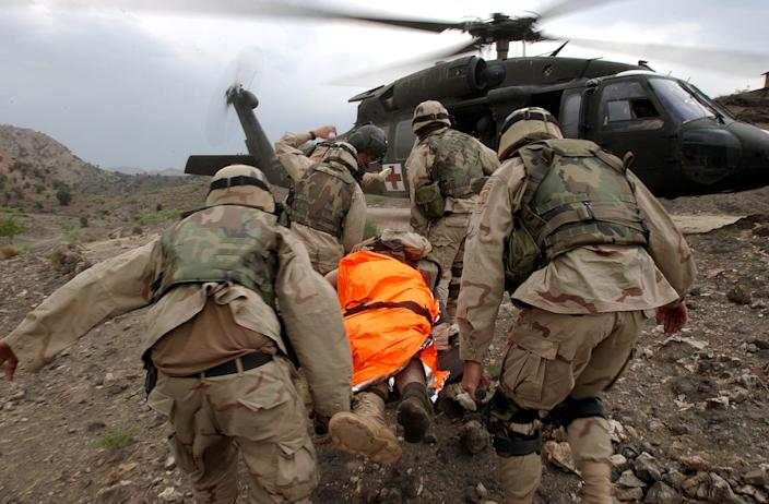 An American soldier is evacuated to the rescue helicopter after being shot near the village of Zunchorah in the Khost near the Pakistani border on April 1, 2004 , about 250 km (156 miles) southwest of Kabul, Afghanistan. (Emilio Morenatti/AP)