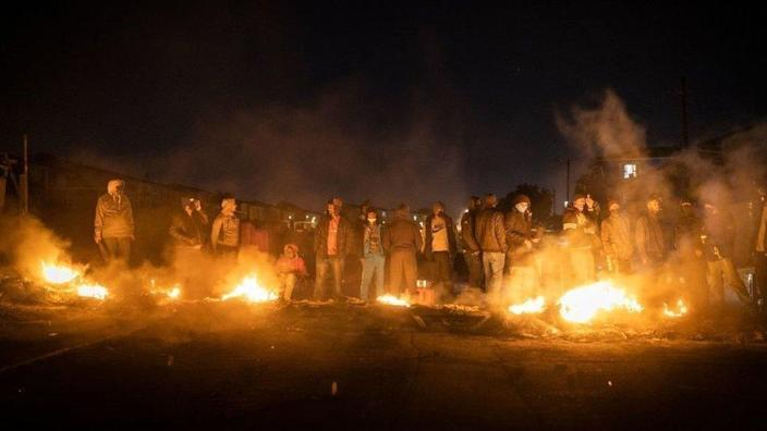 On July 15, 2021, members of the armed community gathered around the fire to keep warm at a roadblock set up in Phoenix Town, North Durban to prevent looters from entering the community.