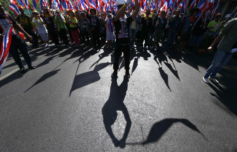 Anti-government protesters wave national flags while marching during a rally Wednesday, Jan. 15, 2014, in Bangkok, Thailand. Thailand's Prime Minister Yingluck Shinawatra said Wednesday that elections due in less than three weeks will go ahead despite intense pressure by her opponents to postpone the vote. The vow came after an overnight shooting attack on anti-government protesters in Bangkok wounded two people and ratcheted up tensions in the country's deepening political crisis. (AP Photo/Wason Wanichakorn)