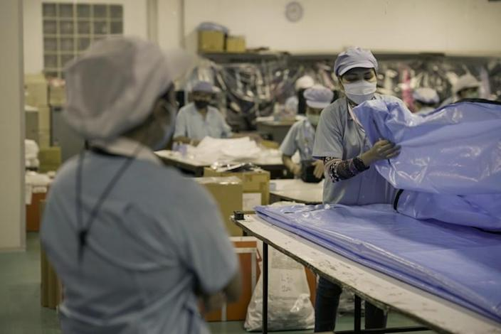 """About 200 workers bustle around Winbest Industrial factory in Thailand as they manufacture shower caps, ponchos and aprons — and body bags. <span class=""""copyright"""">(Caleb Quinley / For The Times)</span>"""