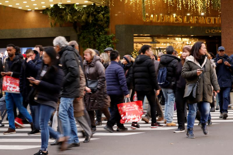People with shopping bags cross the street outside the Galeries Lafayette's department store during the holiday season in Paris
