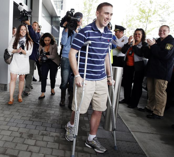 Transit police officer Richard Donohue, center, leaves Spaulding Rehabilitation Hospital in Boston, followed by his wife Kim, left, Friday, June 14, 2013. Donohue was injured during a shoot-out with the Boston Marathon bombing suspects. (AP Photo/Michael Dwyer)