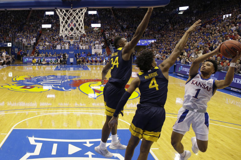Kansas' Devon Dotson (1) shoots under pressure from West Virginia's Miles McBride (4) and Oscar Tshiebwe (34) during the first half of an NCAA college basketball game Saturday, Jan. 4, 2020, in Lawrence, Kan. (AP Photo/Charlie Riedel)