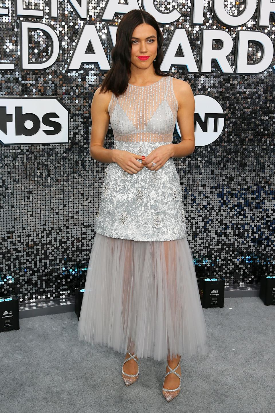 """<h2>Nina Kiri in Georges Chakra</h2><br>Silver on a silver carpet can be hard to pull off, but <em>Handmaid Tale</em>'s Nina Kiri does it with ease in this silver, sequin-covered frock.<span class=""""copyright"""">Photo by JEAN-BAPTISTE LACROIX/AFP via Getty Images.</span>"""