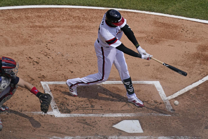 Chicago White Sox's Luis Robert hits a single on a ground ball to Cleveland Indians third baseman Jose Ramirez during the first inning of a baseball game in Chicago, Sunday, May 2, 2021. (AP Photo/Nam Y. Huh)