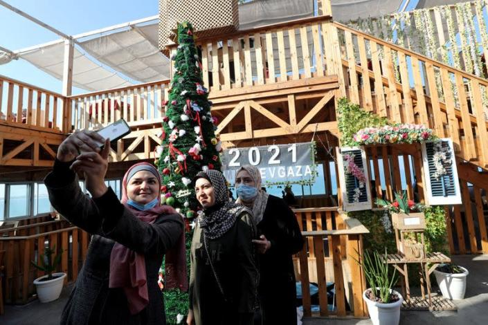 """Palestinian women pose for a picture in front of a Christmas tree at the """"Maldive Gaza"""" cafe on a beach in Gaza City"""