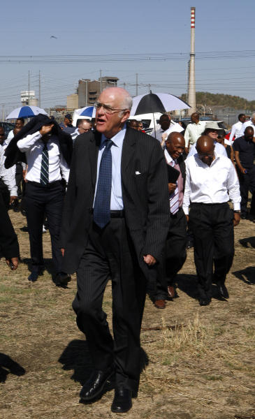 Retired judge Ian Farlam and his team as they inspect the area where the bodies of mine workers were found after the shootings at Lonmin's platinum mine in Marikana near Rustenburg, South Africa, Monday, Oct. 1, 2012. An official inquiry into the killings of dozens of people near a South African platinum mine began Monday even as labor unrest continued with workers at other mines as well as truck drivers continuing protests over pay. (AP Photo/Themba Hadebe)
