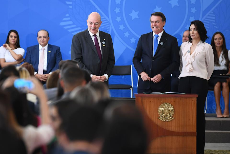 Brazilian President Jair Bolsonaro (2-R), his wife Michelle Bolsonaro and the Minister of Citizenship, Osmar Terra, attend the commemoration ceremony of the National Volunteer Day, at Planalto Palace in Brasilia, on August 28, 2019. - Bolsonaro on Wednesday repeated a demand for French leader Emmanuel Macron to withdraw recent remarks, as he accused France and Germany of