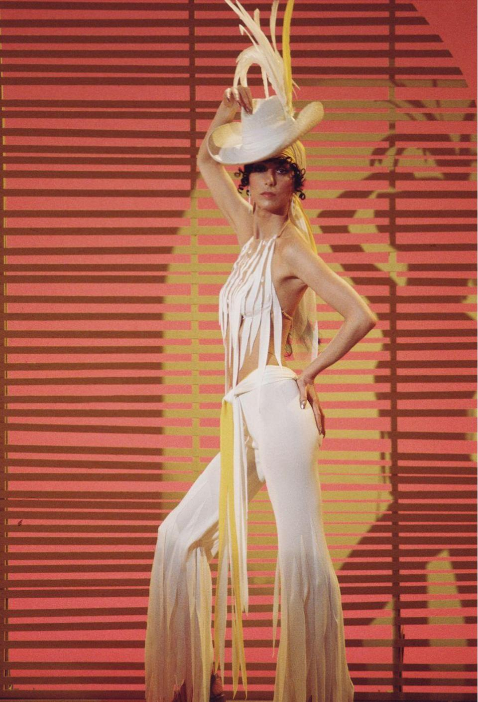 <p>On the <em>Sonny and Cher</em> show in a white hat, cutout halter top, and tiered pants. </p>