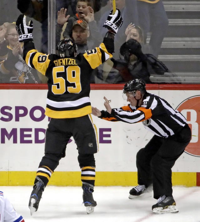 Pittsburgh Penguins' Jake Guentzel (59) celebrates after scoring his 40th regular season goal as referee Kelly Sutherland (11) gets out of his way during the third period of an NHL hockey game against the New York Rangers in Pittsburgh, Saturday, April 6, 2019. (AP Photo/Gene J. Puskar)
