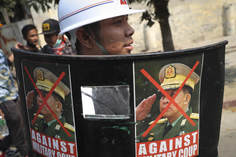 A protester holds a makeshift shield with photos denouncing coup leader Min Aung Hlaing during a demonstration in Mandalay, Myanmar, Saturday, March 6, 2021. The U.N. special envoy for Myanmar on Friday called for urgent Security Council action, saying about 50 peaceful protesters were killed and scores were injured in the military's worst crackdowns this week. (AP Photo)
