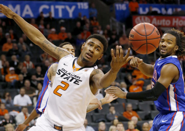 Oklahoma State wing Le'Bryan Nash (2) reaches for the ball in front of Louisiana Tech forward Chris Anderson (5) in the first half of an NCAA college basketball game in Oklahoma City, Saturday, Dec. 14, 2013. (AP Photo/Sue Ogrocki)