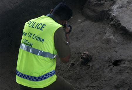 A police officer takes a picture of a human skull at a construction site in the former war zone in Mannar, about 327 km (203 miles) from the capital Colombo, January 16, 2014. REUTERS/Dinuka Liyanawatte