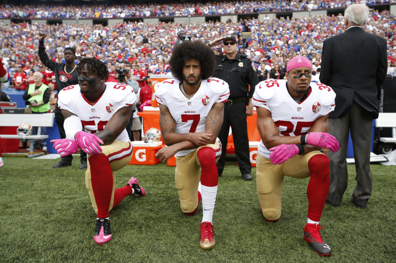 Colin Kaepernick and teammates kneel in 2016. (Photo by Michael Zagaris/San Francisco 49ers/Getty Images)