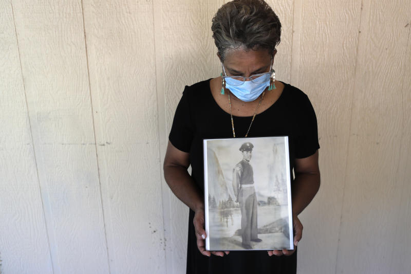FILE - In this May 18, 2020, file photo, Belvin Jefferson White poses with a portrait of her father Saymon Jefferson at Saymon's home in Baton Rouge, La. Belvin recently lost both her father and her uncle, Willie Lee Jefferson, to COVID-19. African Americans are disproportionately likely to say a family member or close friend has died of COVID-19 or respiratory illness since March, according to a series of surveys conducted since April that lays bare how black Americans have borne the brunt of the pandemic. (AP Photo/Gerald Herbert, File)
