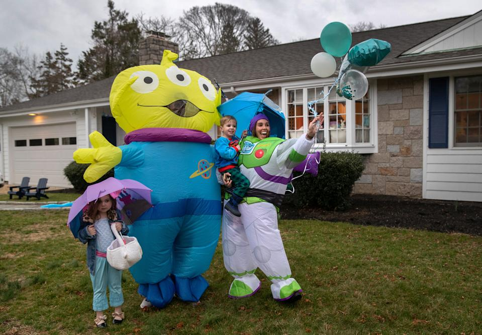 """STAMFORD, CT  - MARCH 28: Lindsay Shea holds her son Kellen as the family watches a caravan of cars pass by to wish him a socially distanced happy third birthday in front of their home on March 28, 2020 in Stamford, Connecticut. Families across the country are finding new ways to celebrate milestone celebrations during the coronavirus (COVID-19) pandemic. The """"birthday train"""" was organized by the Shippan Point Association, a neighborhood organization in Stamford, CT.  (Photo by John Moore/Getty Images)"""