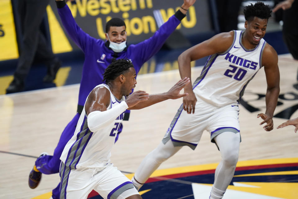 Sacramento Kings guard Buddy Hield, front left, runs off the court as teammates pursue him after he scored the winning basket in overtime of the team's NBA basketball game against the Denver Nuggets on Wednesday, Dec. 23, 2020, in Denver. (AP Photo/David Zalubowski)