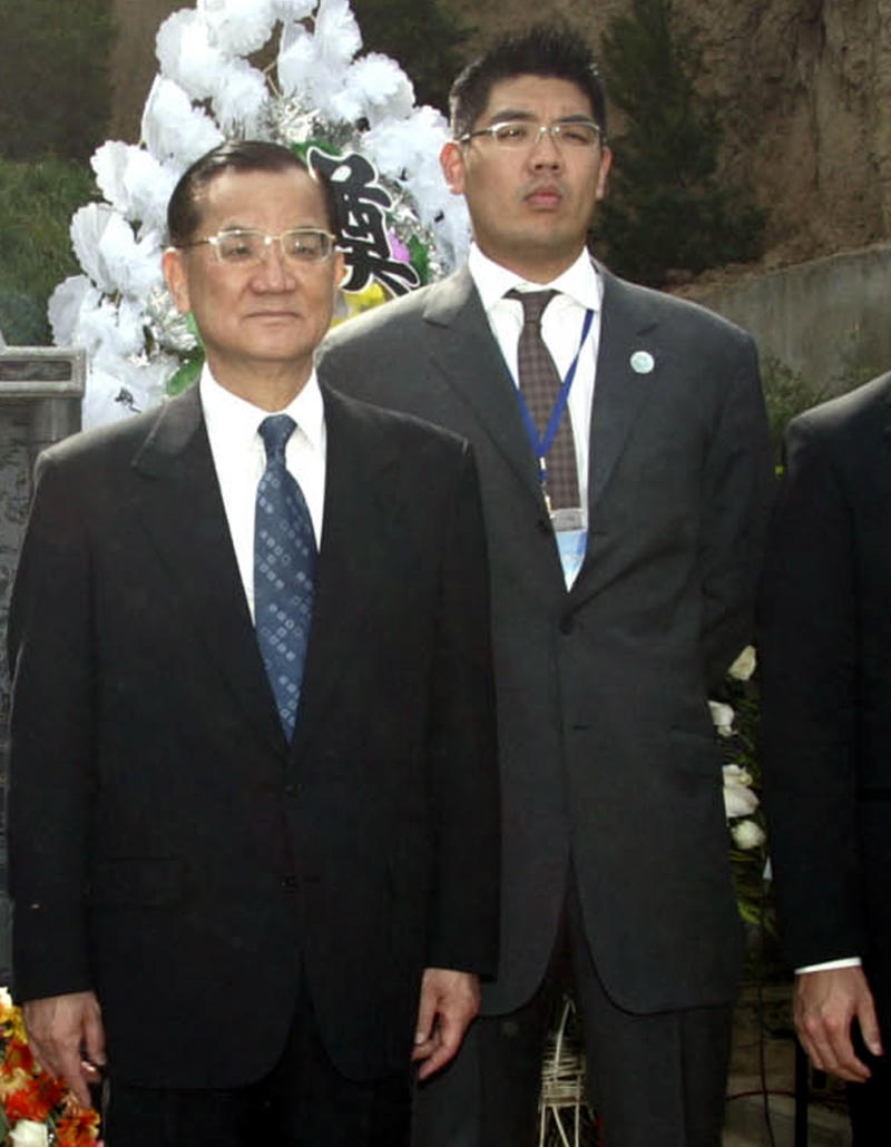 FILE -- In this file photo taken on May 1, 2005, former Taiwanese Vice President  Lien Chan, left,  and Lien Sheng-wen, his elder son, right, along with other family members, unseen, pose for photos at the grave site of Lien Chan's grandmother, Madam Shen in Xia'an, western China.  Lien Sheng-wen was shot in the head and critically wounded while speaking Friday, Nov. 26, 2010,  at a campaign rally in suburban Taipei, local media have reported.  (AP Photo/Song Hongmei, File)