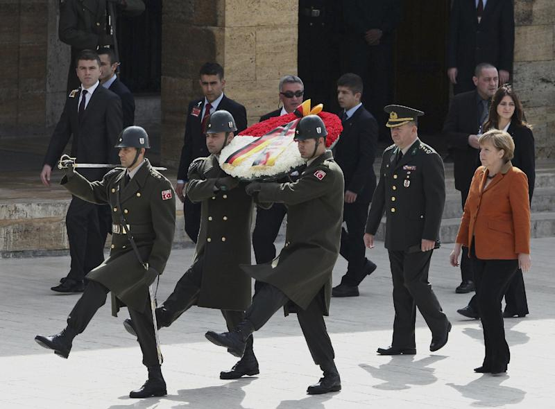 German Chancellor Angela Merkel, right, and Turkish army Col. Muzaffer Taytak, second right, follow a Turkish honour guard as she visits the mausoleum of Turkey's founder Kemal Ataturk in Ankara, Turkey, Monday Feb. 25, 2013. Merkel has visited Sunday German troops deployed to operate Patriot missile batteries in Turkey in a NATO operation to bolster the border with Syria. The chancellor's first stop was Kahramanmaras, some 100 kilometers (60 miles) from the Syrian border, where some 300 German troops are manning two out of six NATO-deployed anti-missile batteries.(AP Photo/Burhan Ozbilici)